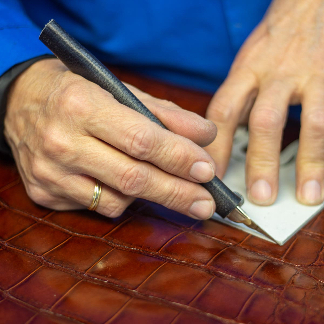 Hand cutting alligator exotic leather