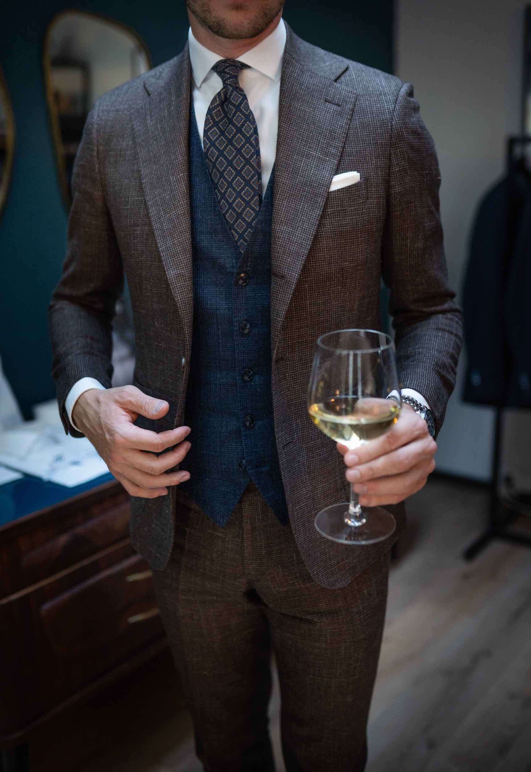 Man with suit and glass of champagne at Dalbiondo's show-room